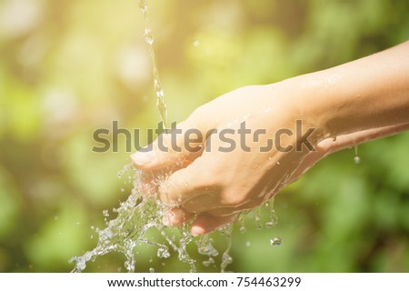 Woman washing hand outdoors. . Young hands with water splash, selective focus #754463299
