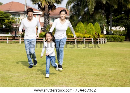 happy asian family running in the park. daughter mother and father. #754469362