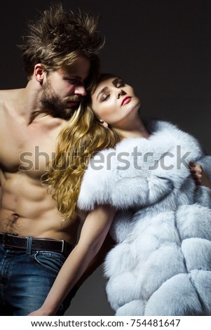 Woman in fur vest and man with muscular torso. Girl with long hair and macho with abs. Couple in love on grey background. Fashion, style, winter clothing. Desire, flirt, relationship. #754481647