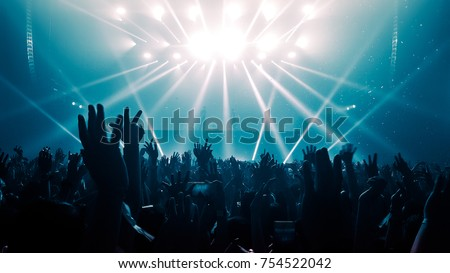 Happy people dance in nightclub light party concert bar and listen to the night music from DJ on the stage in the background. Royalty-Free Stock Photo #754522042