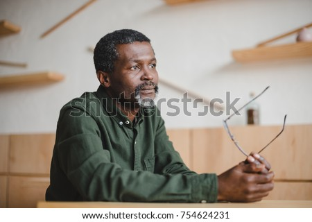 thoughtful mature african american man sitting in cafe #754624231