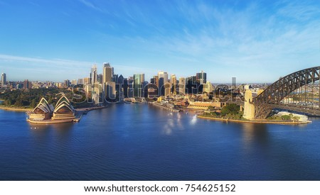 Landmarks of Sydney city CBD on Harbour waterfront around Circular Quay with arch of the Sydney Harbour bridge in warm light of morning sun under blue sky. Royalty-Free Stock Photo #754625152