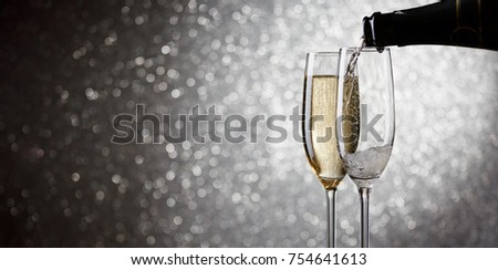 Photo of bottle with pouring wine in wine glasses on gray background #754641613