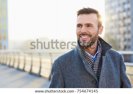 Happy man standing outdoors during sunny winter day #754674145