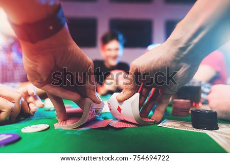 Young people play poker at the table. On the table they have glasses with alcoholic beverages, mobile phones and chips for the game. They have fun playing a game. Royalty-Free Stock Photo #754694722