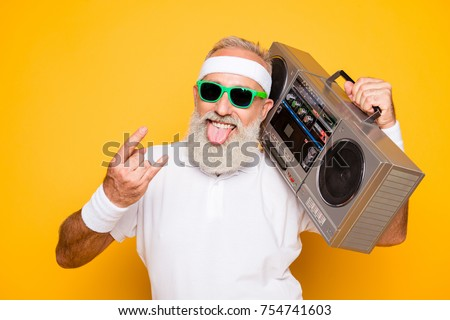 Cheerful excited aged funny active sexy athlete cool pensioner grandpa in eyewear with bass clipping ghetto blaster recorder. Old school, swag, sticking tongue, fooling, gym, workout, technology #754741603