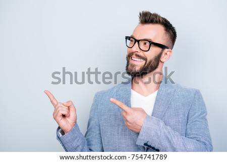 Close up portrait of young successful brunete bearded stock market broker guy on the pure light background, he is smiling, wearing suit and is pointing on a copyspace with his fingers #754741789