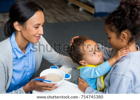 african american mother and daughter feeding little baby boy with porridge #754745380