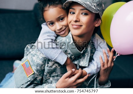 african american daughter hugging her mother in military uniform with balloons at home Royalty-Free Stock Photo #754745797