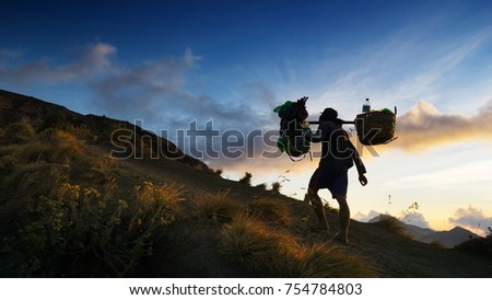 MOUNT RINJANI, LOMBOK, INDONESIA. SEPT 16th 2017:Porter from Mt. Rinjani at the end of a long day, hiking in flip flops with 30 kilos on his shoulder at Sembalun Crater Rim. #754784803