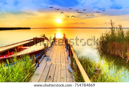 Wharf of wood in the Lake under the sunset #754784869