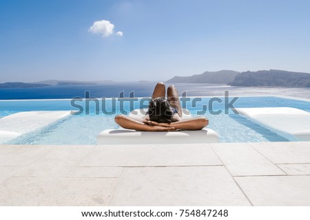 young woman in the swimming pool ,infinity pool relaxing looking out over the ocean caldera of Oia Santorini Greece #754847248