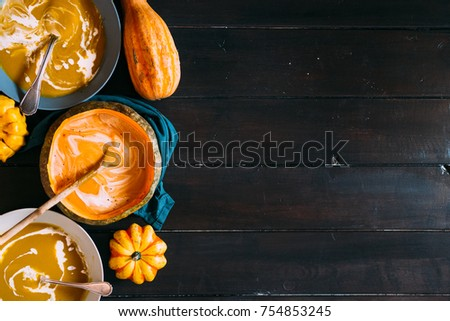 Fall concept, with soup of pumpking inside a pumpkin and potatoes soup on glass with swirl of sour cream and ornamental pumpking around #754853245