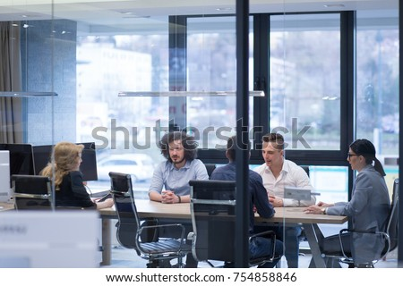 Group of a young business people discussing business plan at modern startup office building #754858846