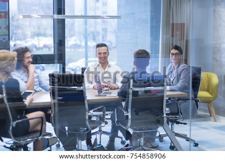 Group of a young business people discussing business plan at modern startup office building #754858906