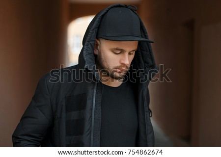 Handsome young guy model in a hood with a black stylish baseball cap and winter jacket posing on the street #754862674