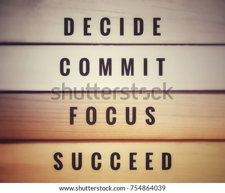 Motivational and inspirational quotes - Decide, commit, focus, succeed. With blurred vintage styled of wooden background.