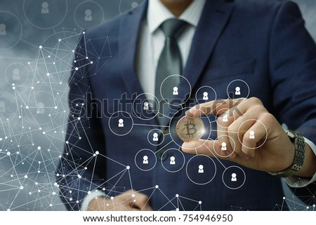 Businessman holding a coin in the network with a blue background. #754946950