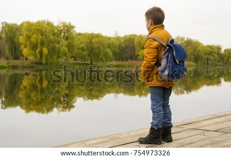 Boy in jacket with backpack standing at the pier #754973326
