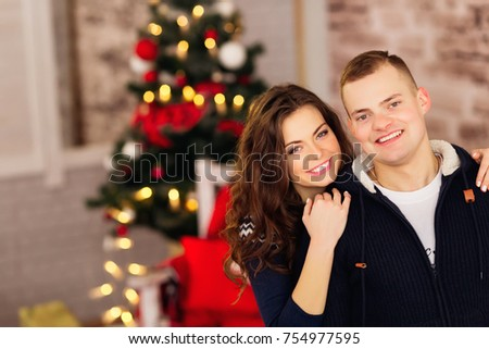 winter, fashion, couple, christmas and people concept - smiling man and woman hugging over holidays lights background #754977595