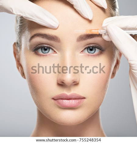 Portrait of young Caucasian woman getting botox cosmetic injection in forehead. Beautiful woman gets botox injection in her face. #755248354