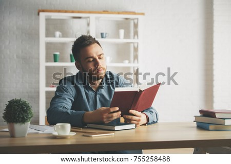 Portrait of attractive young businessman reading at workplace. Education concept  #755258488