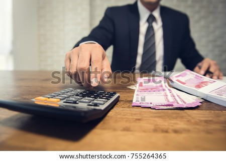 Businessman pressing calculator calculating the conversion rate of Indian Rupee money as a return of financial invesment at the table in his office #755264365