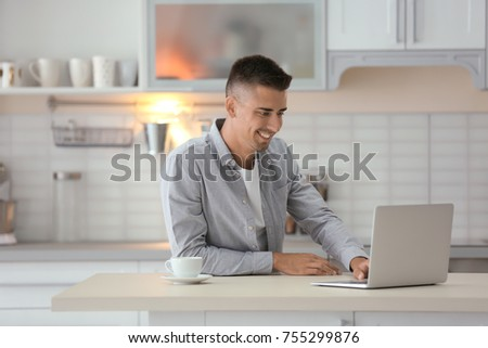 Young man using laptop at table in kitchen #755299876