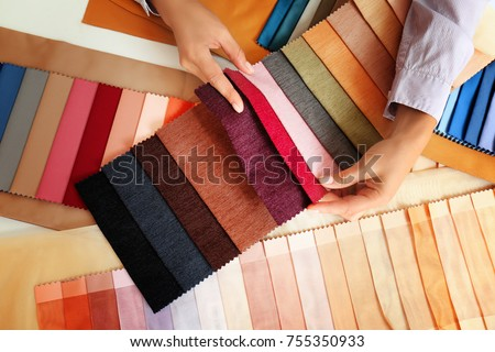 Young woman with fabric samples for curtains at table Royalty-Free Stock Photo #755350933