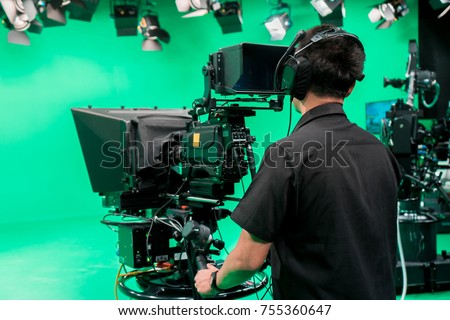 Cameraman taking a broadcast camera  in broadcast television virtual green screen studio room. Royalty-Free Stock Photo #755360647