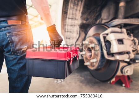 The abstract image of the back of technician hold a toolbox and blurred disc brake is backdrop. the concept of automotive, repairing, mechanical, vehicle and technology. #755363410