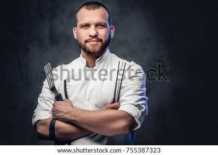 Chef cook holds a knife over dark grey background. Royalty-Free Stock Photo #755387323