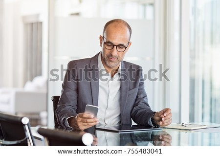 Mature business man in formal clothing wearing spectacles using mobile phone. Serious businessman using smartphone and digital tablet at work. Manager in suit using cellphone in a modern office. Royalty-Free Stock Photo #755483041