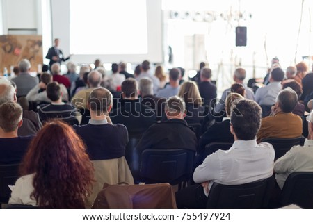 Speaker giving a talk in conference hall at business event. Audience at the conference hall. Business and Entrepreneurship concept. Focus on unrecognizable man in the audience. #755497924