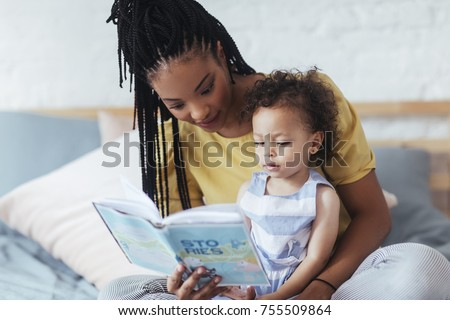 Beautiful African woman sitting on bed and reading a book to her cute baby daughter. #755509864