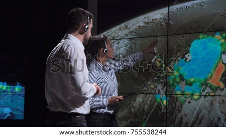 Group of two scientists observing and tracking hurricane on map and analyzing weather. Elements of this image furnished by NASA.