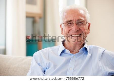Portrait Of Smiling Senior Man Sitting On Sofa At Home #755586772