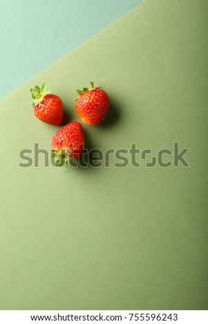 Three strawberries on green background, food above #755596243
