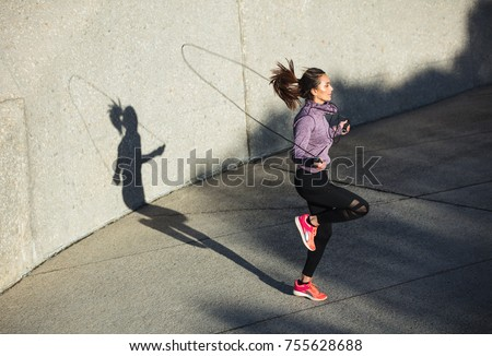 Fitness woman skipping with a jump rope outdoors. Female doing fitness training in morning. Royalty-Free Stock Photo #755628688