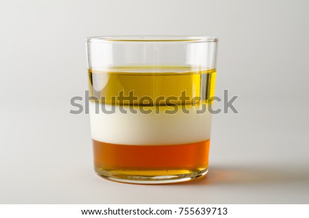 Physics. Density column. Laboratory glassware containing separed layers of vegetable oil, milk and honey. Royalty-Free Stock Photo #755639713
