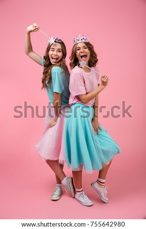 Full length of cheerful laughing girls friends dressed in princess costumes holding magical wands and looking camera isolated over pink background #755642980