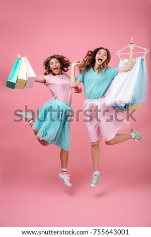 Full length portrait of two excited joyful girls dressed in bright colorful clothes holding shopping bags and jumping isolated over pink background #755643001