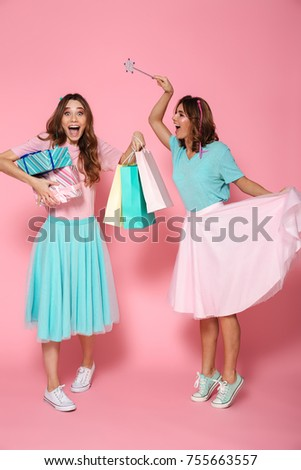 Full length photo of two happy woman having fun with magic wand, isolated on pink background #755663557