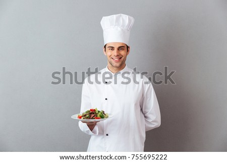 Picture of happy young cook in uniform standing isolated over grey wall background. Looking camera holding salad.
