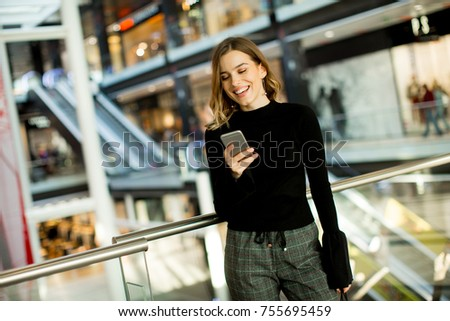 Portrait of lovely young woman looking on mobile phone in shopping center #755695459