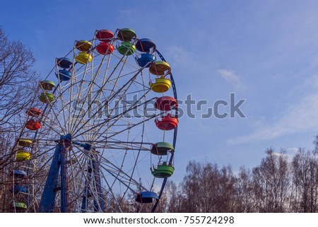 Autumn Park. Ferris wheel with colored baskets. #755724298