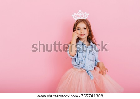 Pretty sweet little girl with long brunette hair in tulle skirt holding white crown on head isolated on pink background. Beautiful joyful child expressing true emotions. Place for text #755741308