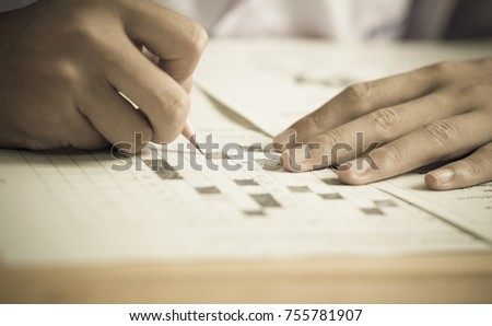 Students concentration holding pencils in hand doing multiple-choice quizzes testing exams answer sheets exercises in school, Tests is concept assessment intended to measure knowledge skill aptitude #755781907