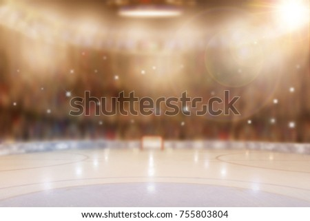 Low angle view of hockey arena with sports fans in the stands. Focus on foreground with deliberate shallow depth of field on background with camera flashes and lens flare effect.