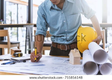 Close up of civil male engineer asian working on blueprint architectural project at construction site at desk in office. #755856148
